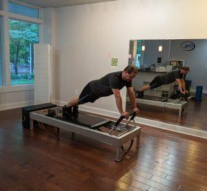 Man demonstrating Pilates Reformer